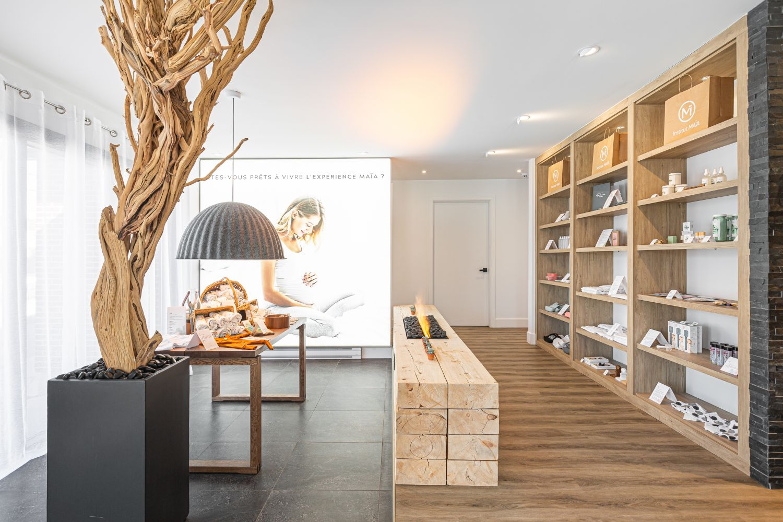 Boutique prénatale zen avec présentoirs et étagères en bois, foyer central moderne et branche d'arbre décorative