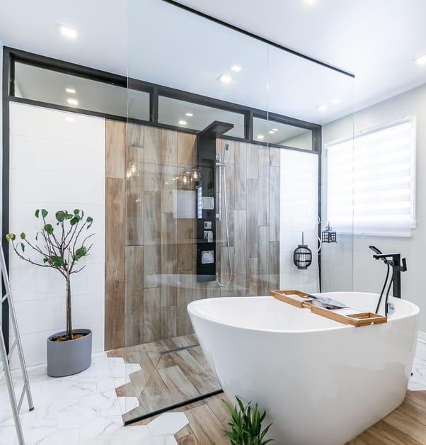Derrière un grand panneau de verre se trouve une douche à l'italienne avec des sections de tuiles blanches et effet bois.