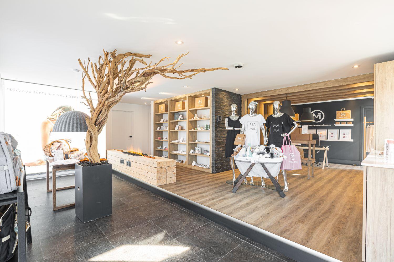 Espace boutique d'une clinique prénatale zen aux accents de bois avec branches décoratives et présentoirs