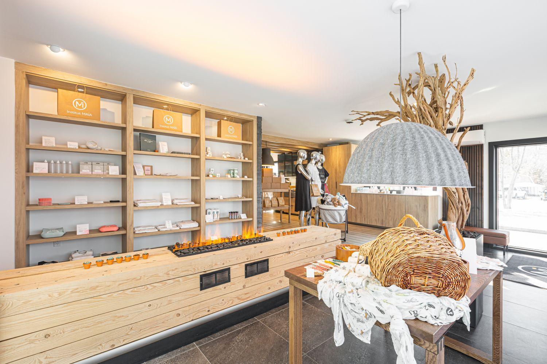 boutique prénatale zen avec luminaire suspendu gris au-dessus d'un présentoir et étagères murales en bois