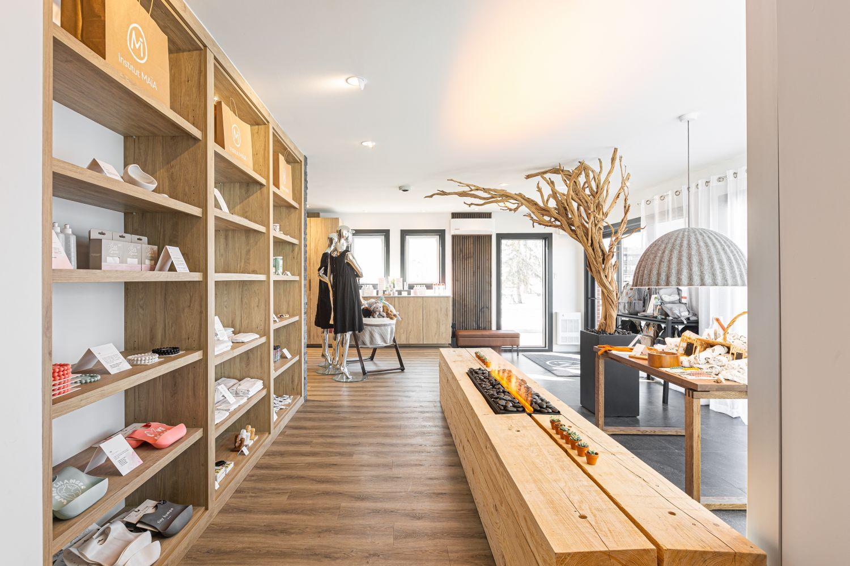 Espace boutique avec grandes étagères murales en bois face à un foyer contemporain