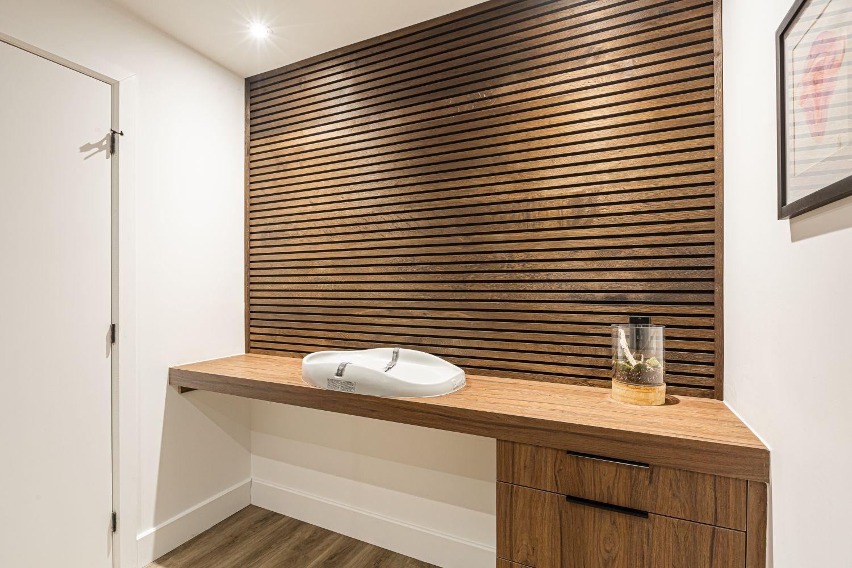 salle à langer chaleureuse avec mobilier sur mesure et mur en lattes de bois