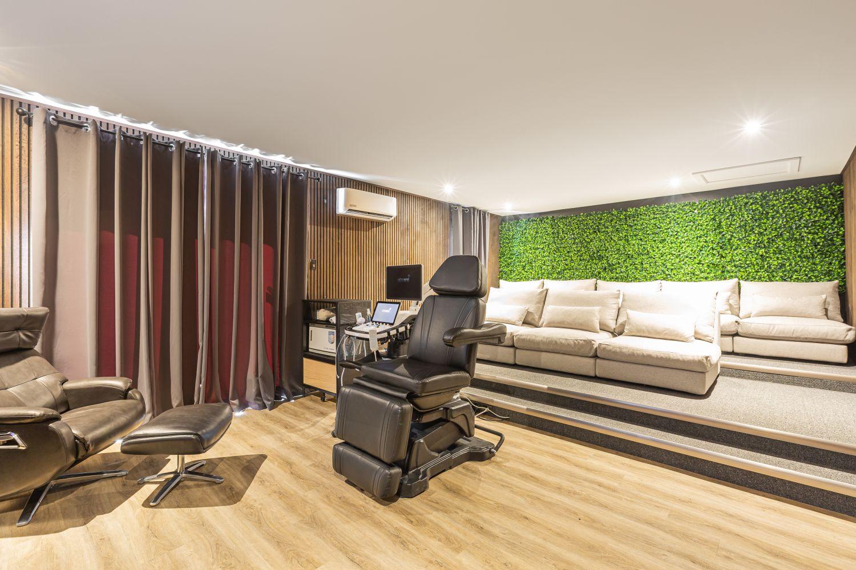 Gros fauteuils beiges dans une salle de projection d'échographies avec mur végétal et en bois
