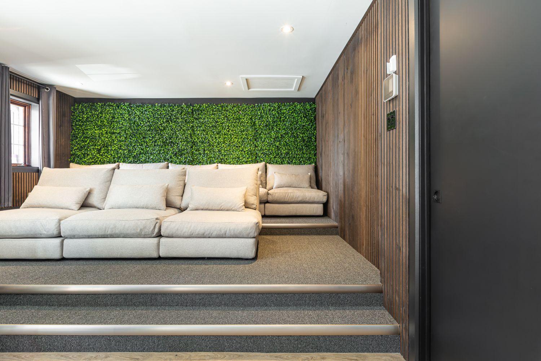 Salle de visionnement moderne avec rangées de grands fauteuils en tissu beige et mur végétal à l'arrière