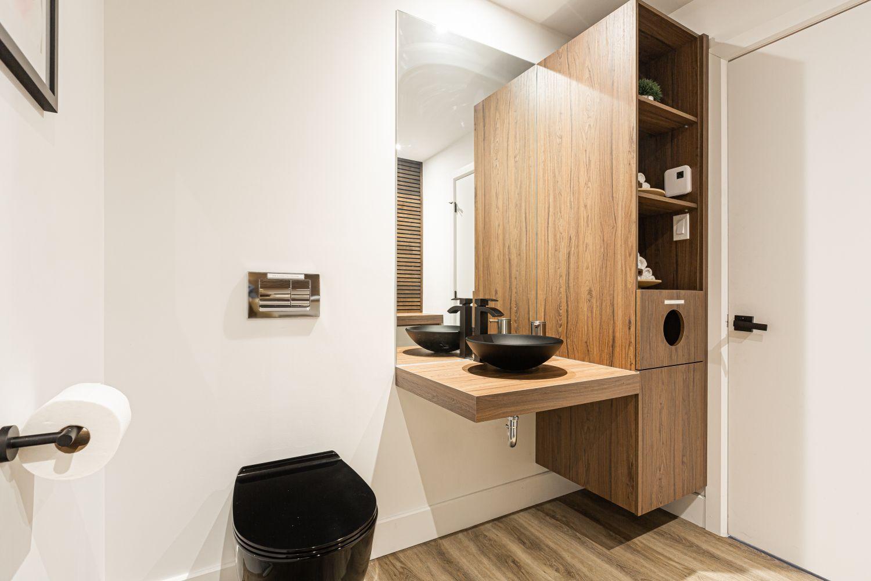 Salle d'eau avec toilette et lavabo noirs et mobilier en bois foncé