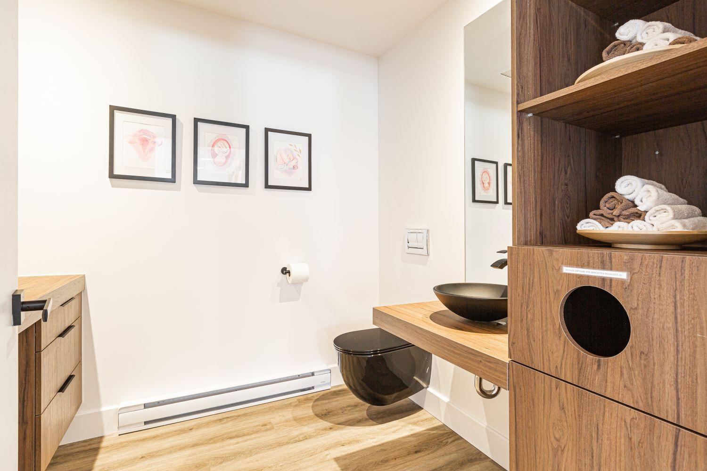 Salle d'eau épurée avec murs blancs, petits cadres photos et meuble de rangement en bois