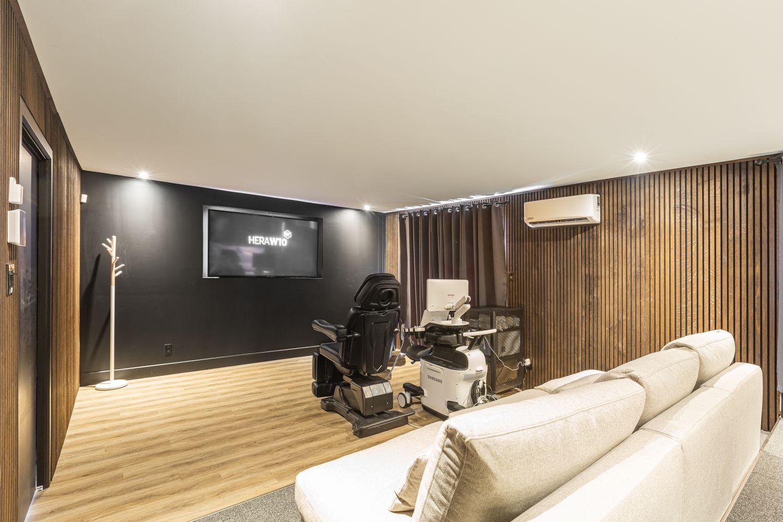 Salle de projection prénatale avec murs en bois, grand écran et fauteuils beiges