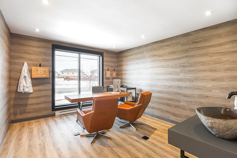 Bureau de consultation lumineux avec grande fenêtre, murs en bois et vasque en pierre