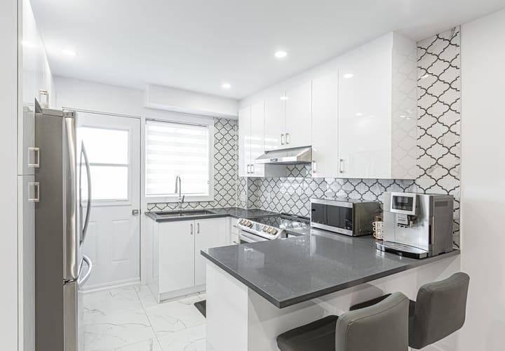 Cuisine contemporaine lumineuse avec des armoires blanches, des comptoirs gris et un dosseret
