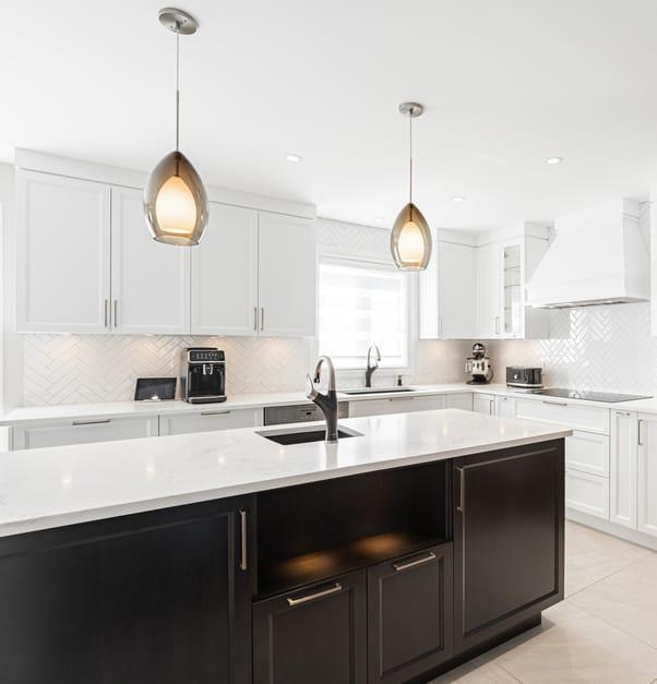 Une cuisine moderne blanche avec un îlot doté d'un comptoir en pierre blanche et d'armoires noires.