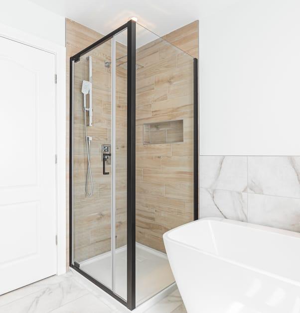 Une douche sans margelle avec des carreaux imitant le bois et une tête de douche en cascade