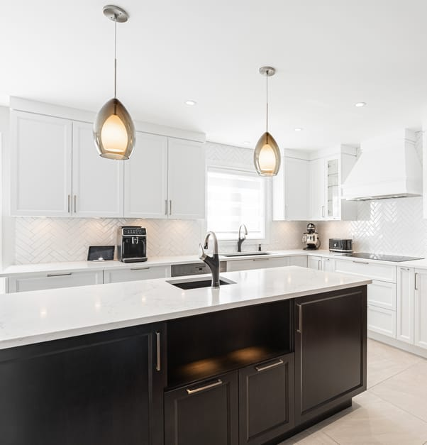 A white modern kitchen with an island that has a white stone countertop and black cabinets