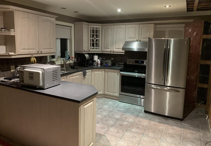 outdated kitchen with beige cabinets and dark countertops