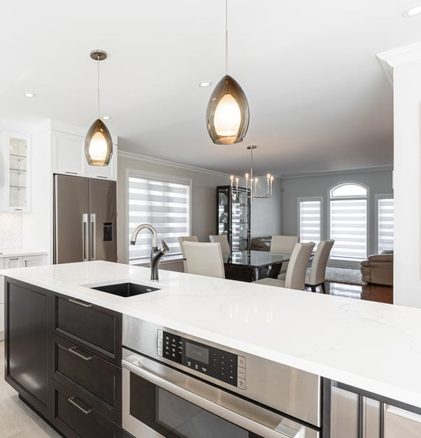 A modern white kitchen with microwave integrated in the central island