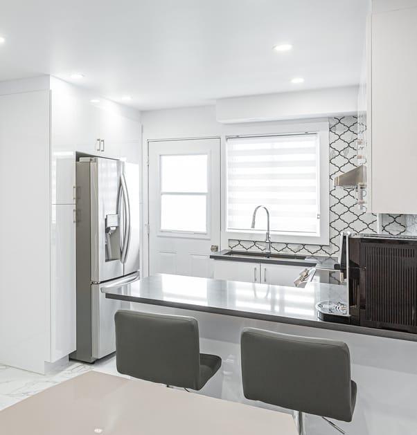 Bright contemporary kitchen with grey quartz countertops and white cabinets
