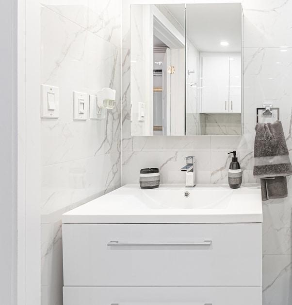 vanité blanche avec pharmacie miroir et murs imitation marbre