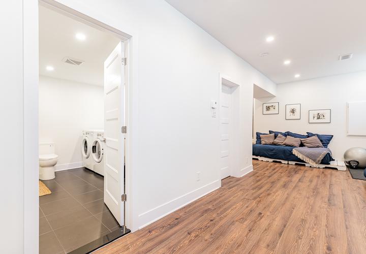 Un couloir avec des murs blancs et un plancher en bois mènent à une salle de bain avec des carreaux de céramique gris, une laveuse et une sécheuse.