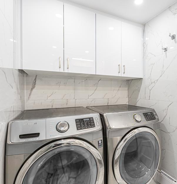 laveuse et une sècheuse grises rangées avec armoires blanches au-dessus