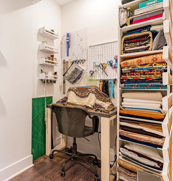 Une table de couture à côté d'un rangement ouvert pour les tissus