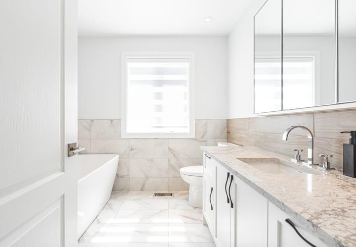 belle salle de bains blanche avec baignoire autoportante et vanité à un seul lavabo avec poignées chromées