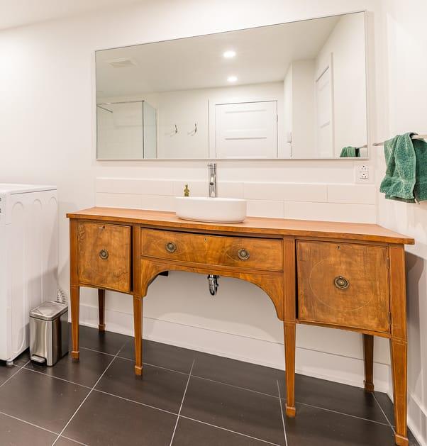 Une salle de bain moderne avec une vanité antique.