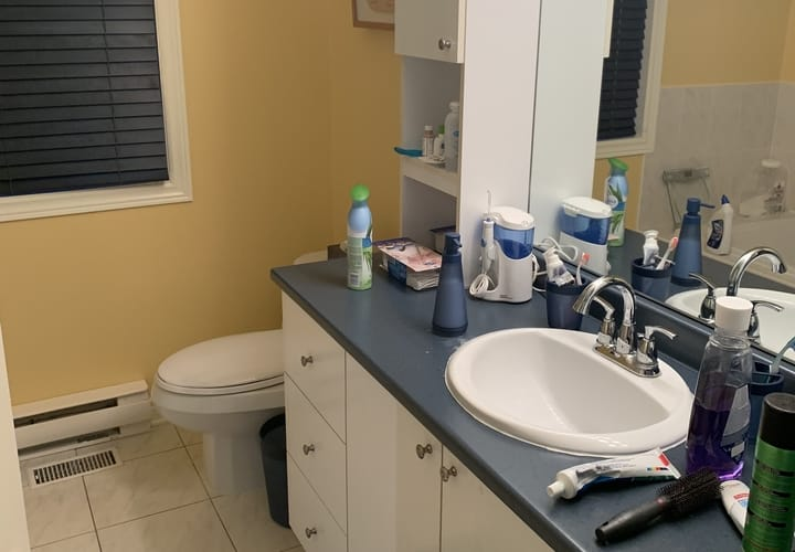 vieille salle de bain avec vanité en mélamine blanche et comptoir bleu
