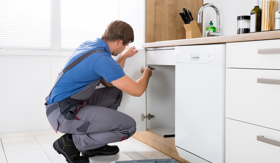 worker working on a kitchen cabinet door in a rental apartment