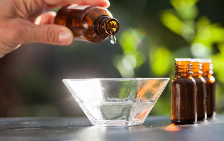 main versant de l'huile essentielle dans un bol pour éliminer fourmis charpentières
