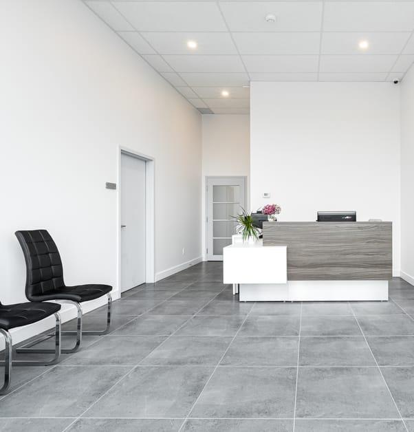 réception de bureau avec chaises en cuir noir, murs blancs et comptoir d'acceuil deux tons