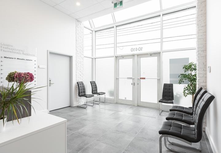 Rénovation d'un bureau commercial avec salle d'attente moderne et chaises en cuir noir