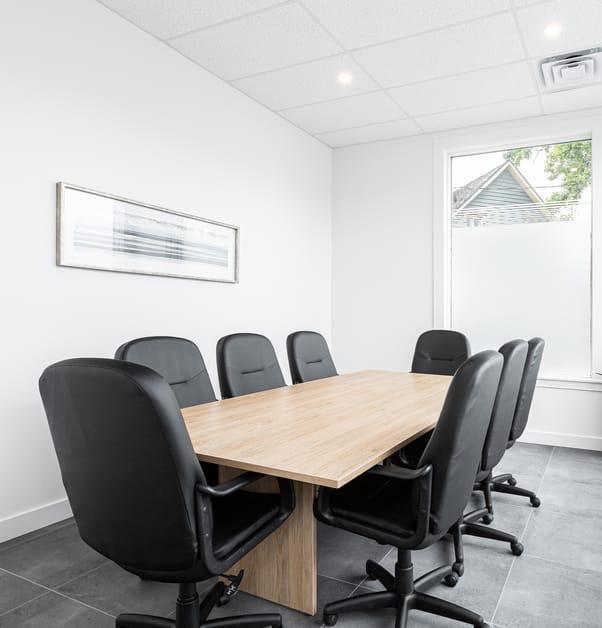 salle de conférence avec une table en bois clair et plusieurs chaises noires